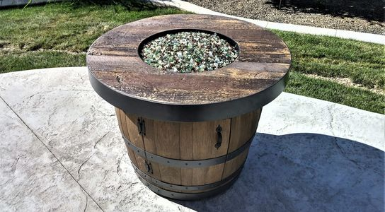 Hand-crafted custom cement portable wine barrel fire table fire pit made to look like wood 88,000 BTUs and 92,000 BTU output Bronze Timber brown tones with golden highlights (also Mystic Fog black and grey tones with white highlights)