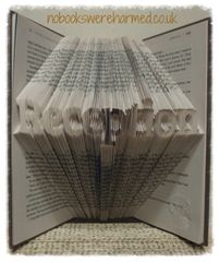 """""""Reception"""" sign, hand folded into the pages of a book."""