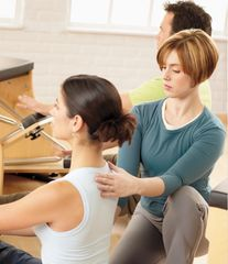 Pilates instructor queuing client on correct postural form