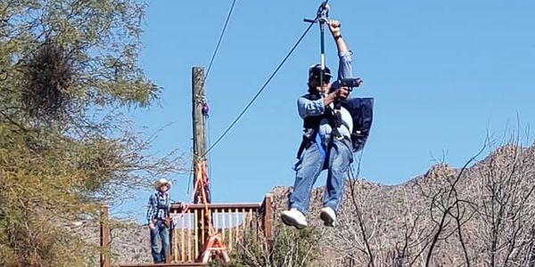 Ziplines Are Active! Ziplining over Old Tucson, gun in hand, shooting carefully at targets set up.