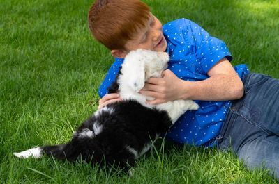 Boy with sheepadoodle puppy