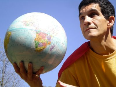 Barry is dressed as a superhero with a yellow shirt and red cape, holding up a globe against a blue