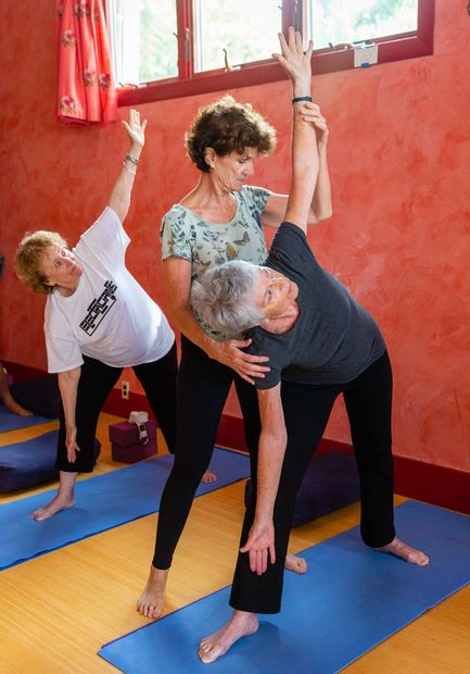 Barbara Lyon assists Senior Yoga students in Triangle Pose