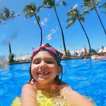 girl using kickboard in swimming pool with maui palm trees behind her