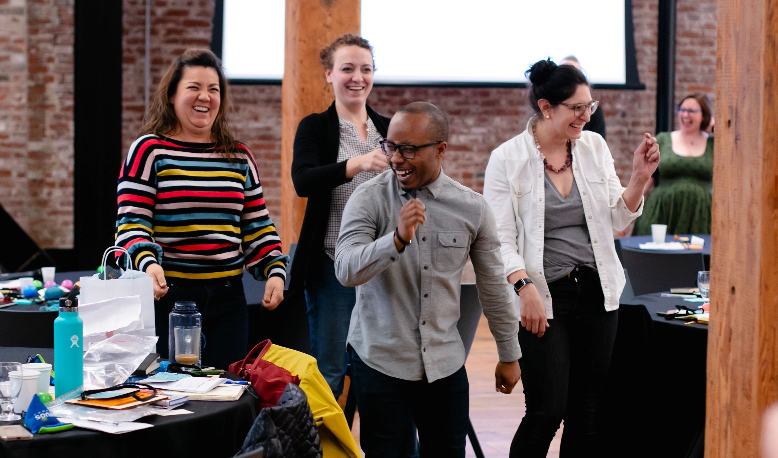 A group of people laughing and moving their bodies at an employee development training.