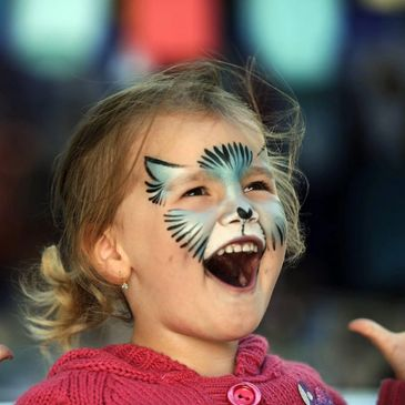 Very excited young girl with mouth open wide with a blue and white cat facepaint