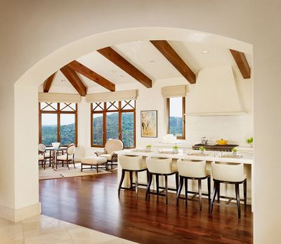 white custom kitchen with wood beams and hillside view