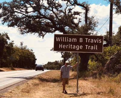 Photo of Casey Cutler and Wm B Travis Trail Sign
