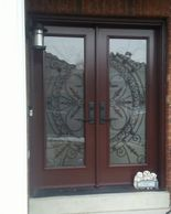 chestnut brown double entry doors with wrought iron.