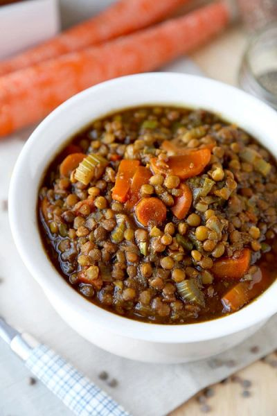 Cooked lentil soup in a white bowl with sliced cooked carrots on top.