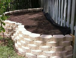 castlewall stone; stone edging; flower bed; retaining wall; shrubs; plants; tree; mulch; raised flower bed