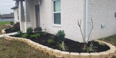 castlewall stone; stone edging; flower bed; retaining wall; shrubs; plants; tree; mulch