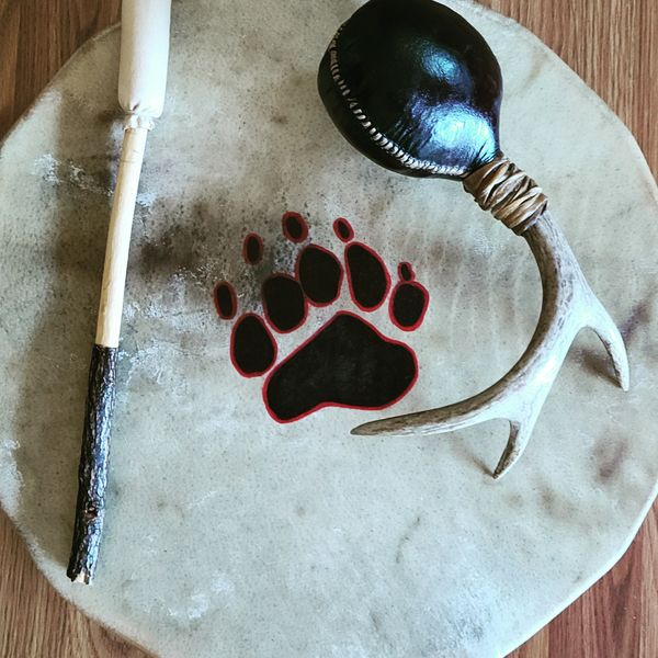 18 jnch Buffalo hide with Bear track and large Elk rattle with Deer antler handle.