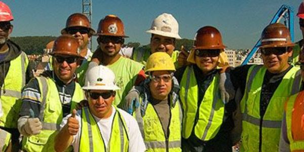 team photo of 9 happy workers in their PPE
