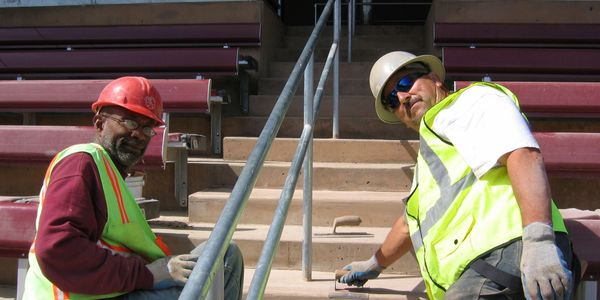two workers taking a break from smooth conrete stairs to smile for a picture