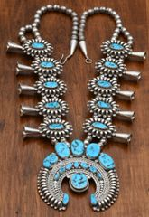 Navajo dead-pawn squash blossom with Sleeping Beauty mine turquoise and intricate silversmithing.