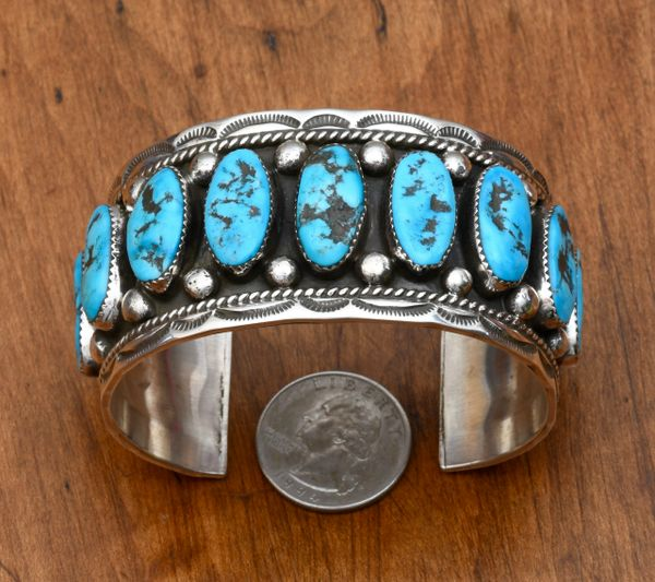Classic Navajo Sterling row cuff with nine oval turquoise stones by Garret Platero.