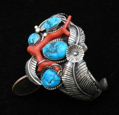 Dead-pawn Navajo cuff with large branch coral and four Sleeping Beauty turquoise stones.