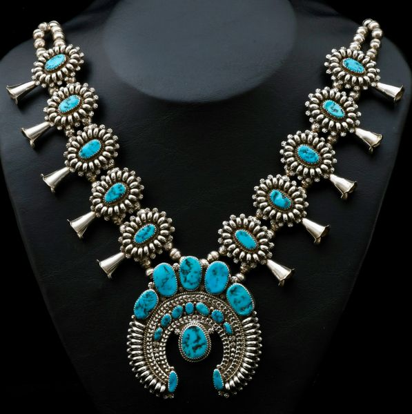Intricate Navajo dead-pawn squash blossom necklace with amazing silver-smithing and 25 pristine Sleeping Beauty Mine turquoise stones.