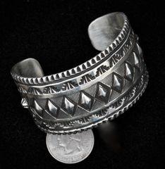 Sterling Navajo deep hand-stamped cuff with diamond-shape repose' by Elvira Bill.
