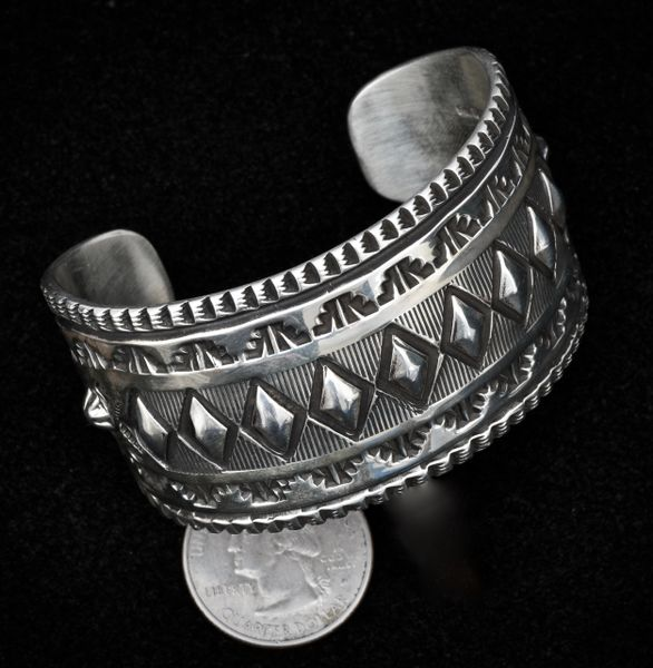 Sterling Navajo deep hand-stamped cuff with diamond-shape repose' by Elvira Bill.