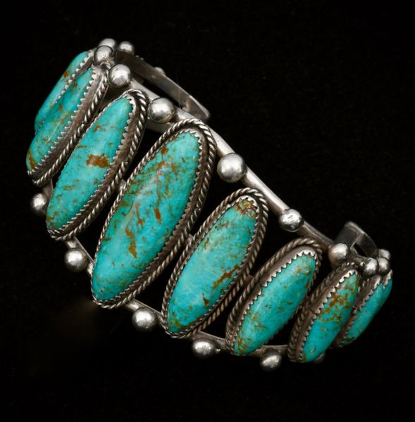 Larger wrist size dead-pawn Navajo row cuff with 11 elongated turquoise stones.