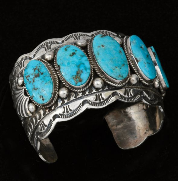 Wide intricately-stamped Navajo row cuff with five Kingman turquoise stones, by Marcella James.