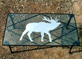 Custom built coffee table.  Steel frame, glass top with an elk inlayed in mirror.