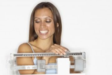 Photo of a woman on a scale weighing herself with a big smile on her face