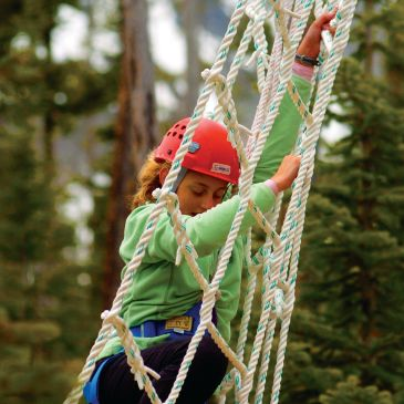 Young camper climbing a cargo net in an obstacle course in Minnesota.