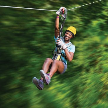 Girl ziplining at an aerial adventure park in Michigan.
