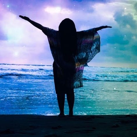 Picture of a woman standing in front of the ocean with her arms wide open.