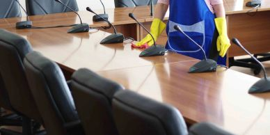 housekeeping lady cleaning the conference table and mic