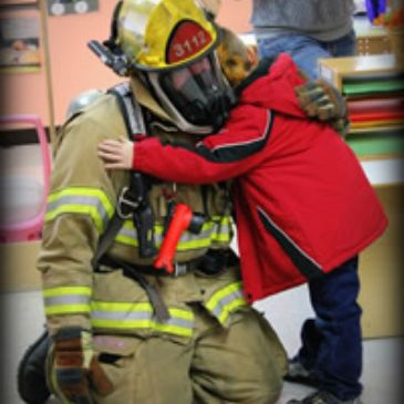 a firefighter in full turnout gear kneeled down getting a hug from a child during a school visit.