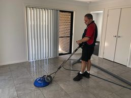 Technician steam extraction cleaning tiles
