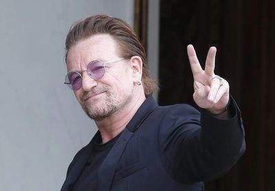 Bono lead singer from U2 holding up a peace sign, wearing glasses