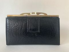 An Unbranded Good Quality Black Textured Leather 1970s Vintage Coin Purse Wallet With Leather outer and inside lining.Brass toned Frame and kiss clasp.