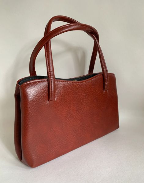 Vintage 1960s Cinnamon Brown Synthetic Handbag Black Fabric Lining And Side Pockets Gold toned fittings and frame.