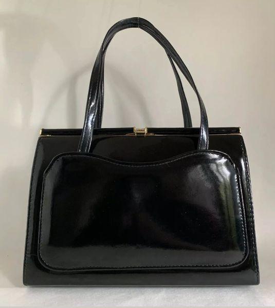 Vintage 1960s Black Faux Patent Handbag With Black Fabric Lining Front Pocket.