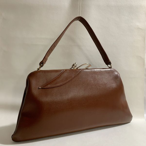 Chic Vintage 1960s Tan Soft Faux Leather Handbag With Dark Cream Fabric Lining And Gold Tone Frame Ornate Clasp.