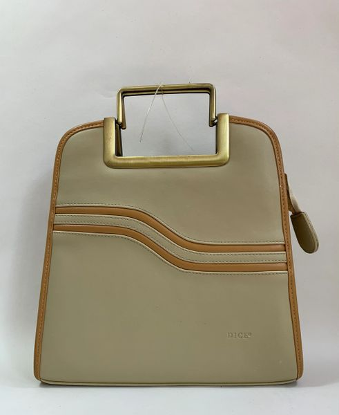 DICE Beige & Tan Synthetic Handbag With Antiqued Brass Tone Metal Handles & Monogrammed Brown Fabric Lining.