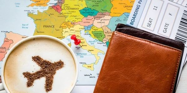 cappucino in mug with airplane made with chocolate, on world map next to passport