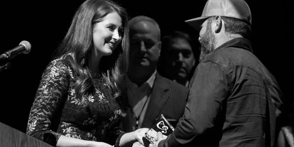 Ashton Campbell Gill presents an award to Heath Sanders during the Arkansas Country Music Awards.