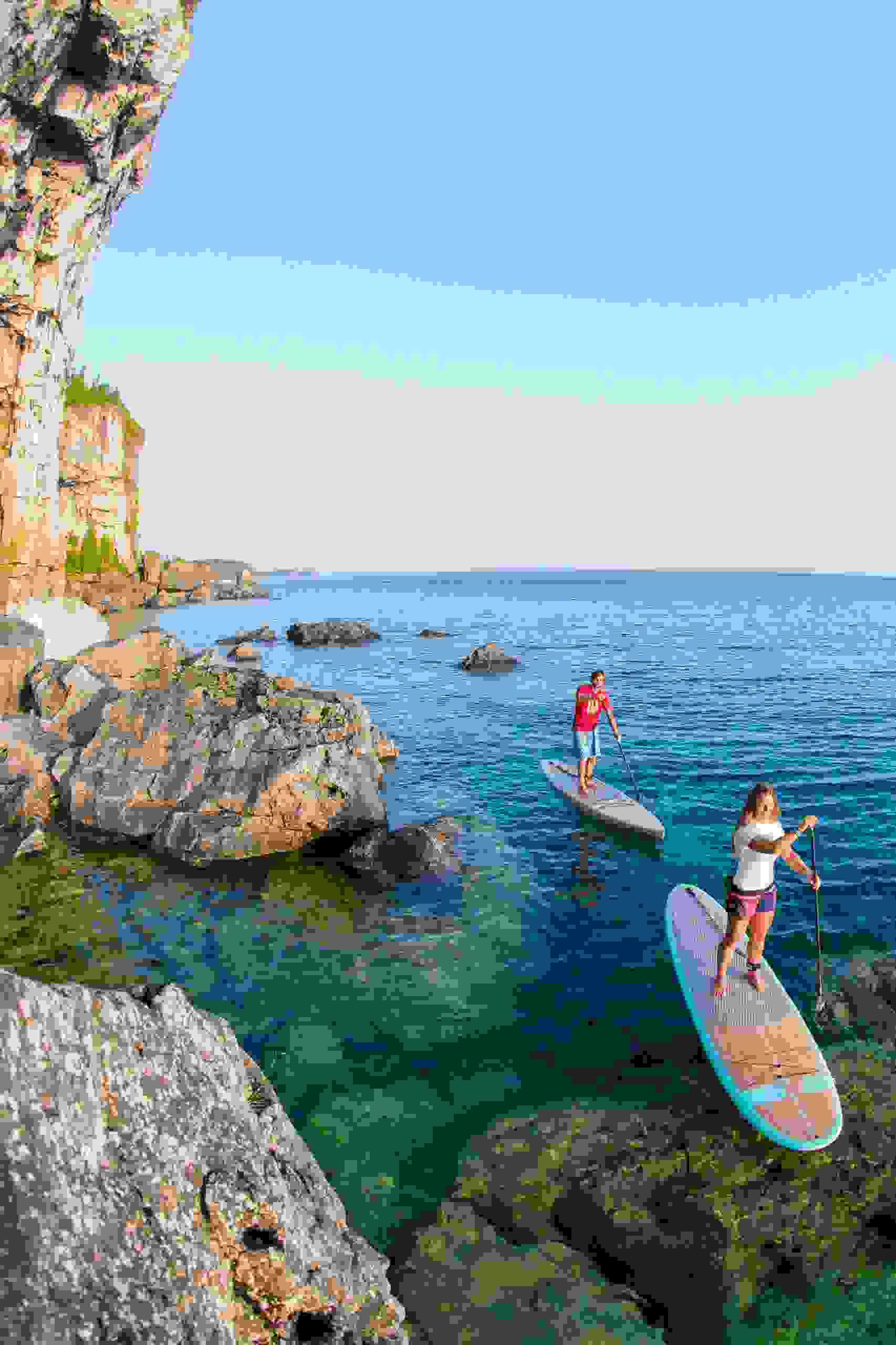 A couple paddle boarding next to high cliffs