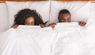 A man and women peering out from beneath their blankets up toward the camera.