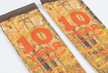 Full-color, sublimated runner's sleeves branded with a 10-yr anniversary race logo featuring autumn.
