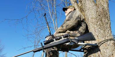 Hunter in a tree stand with a Hip Stick Shooting Rest on his leg and a Gun Holder at his side