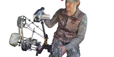 Hunter sitting on a ground blind chair in a tent using a Pic Stick and a Bow Holder to film her hunt