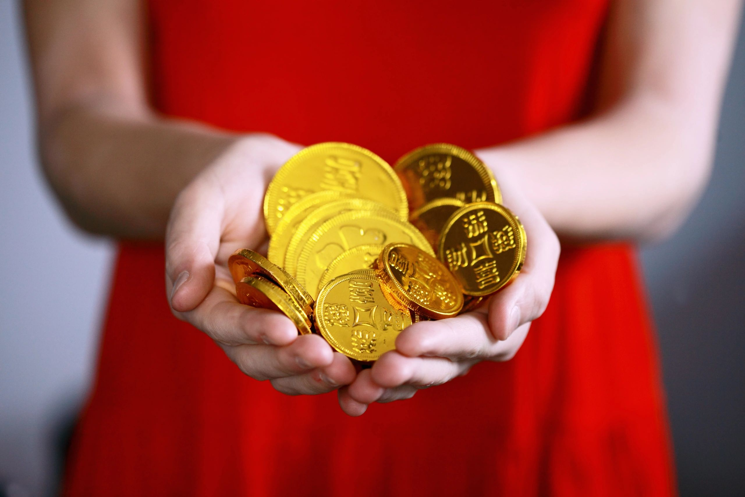 A woman with a handful of gold coins.