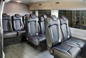 Several rows of black leather minibus seats offering multi-personal seating